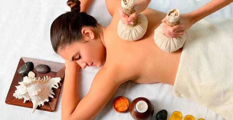 Женщине делают массаж травяными мешочками